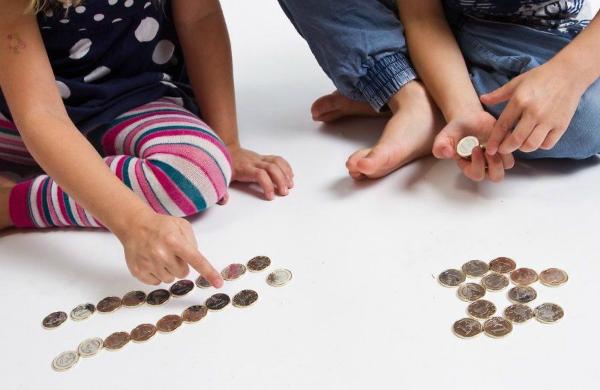 На фото изображены детские руки, считающие копейки.