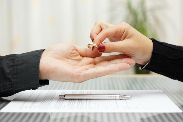На фото изображена пара рук, одна из которых передает другой обручальное кольцо.