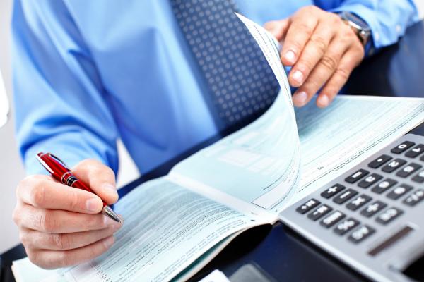 На фото изображены руки мужчины с бумагами и калькулятором.